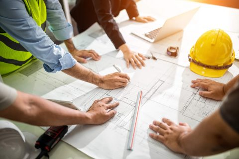 group of people reviewing blueprints for a building