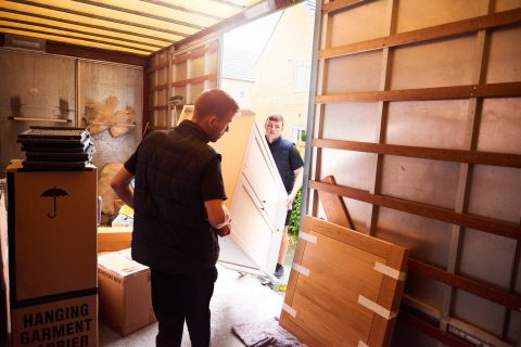 Two men moving a couch out of a moving truck