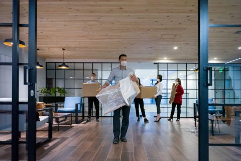 People carrying furniture into office